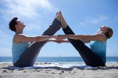 Zwei Frauen, die Yoga am Strand üben Stockfoto