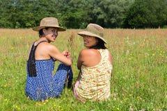 Zwei Frauen, die zurück in blühender Wiese schauen Stockfoto