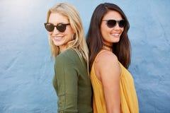 Zwei Frauen, die zurück zu Rückseite lächeln Stockbild
