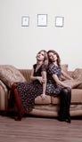Zwei Frauen, die zurück zu Rückseite sitzen Stockfotos