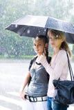 Zwei Frauen in einem riany Wetter stockbilder