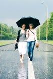 Zwei Frauen in einem starken Regen Stockfotos