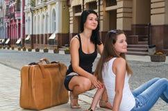 Zwei Frauen am Feiertag, der auf ein Taxi wartet stockfotos