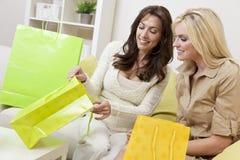 Zwei Frauen-Freunde, die zu Hause in den Einkaufen-Beuteln schauen Lizenzfreies Stockfoto