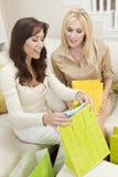 Zwei Frauen-Freunde, die zu Hause in den Einkaufen-Beuteln schauen Stockbilder