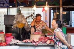Zwei Frauen haben ein Gespräch am nassen Markt Stockfoto