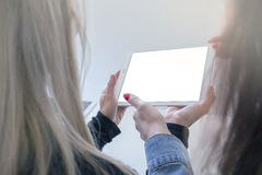 Zwei Frauen halten eine Tablette stockfotografie