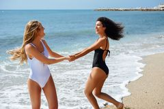 Zwei Frauen im Badeanzug, der Spaß auf dem Strand hat Stockbild