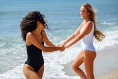 Zwei Frauen im Badeanzug, der Spaß auf dem Strand hat Stockfotos