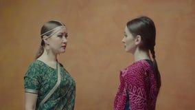 Zwei Frauen im Sari, der jeder des anderen Augen untersucht stock video