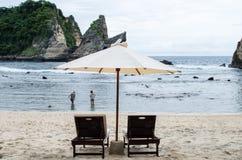 Zwei Frauen im Wasser von Atuh setzen mit den sunbeds auf den Strand, die im Vordergrund Bali, Indonesien zentriert werden Lizenzfreie Stockfotografie