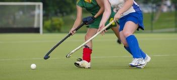 Zwei Frauen kämpfen zur Steuerung des Balls während des Hockeyspiels stockfotos