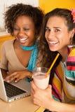 Zwei Frauen am Kaffee unter Verwendung des Laptops Stockfotografie