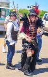 Zwei Frauen kleideten in Steampunk-Kostümen mit Hüten und in den Schutzbrillen draußen mit Gebäuden ein LKW und Männer - selektiv stockbild