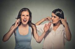 Zwei Frauen laut, abscheuliche unhöfliche Frau, die laut am Handy spricht stockfotografie