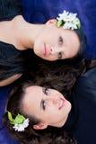 Zwei Frauen mit Blumen im Haar liegen auf einem blauen Hintergrund Lizenzfreie Stockfotos