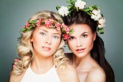 Zwei Frauen mit dem langen gelockten Haar, perfekter Haut und Summe Lizenzfreie Stockfotografie