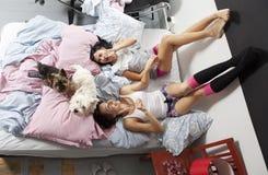 Zwei Frauen mit Hund beim Bettlächeln stockfotos