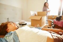 Zwei Frauen mit Kästen im Schlafzimmer, das in neues Haus sich bewegt Stockfotos