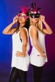 Zwei Frauen mit venetianischen Masken des Karnevals Stockfotos