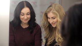 Zwei Frauen passen eine Zeitschrift über Schönheit auf stock video