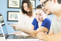Zwei Frauen und ein Mann arbeiten mit Computer Stockbild