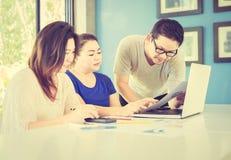 Zwei Frauen und ein Mann arbeiten mit an Computer im modernen Büro Stockfoto