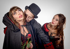 Zwei Frauen und ein Mann in der Verkleidung Halloween stockfotografie
