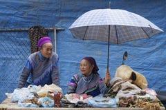 Zwei Frauen unter einem Regenschirm am Markt Lizenzfreie Stockfotos