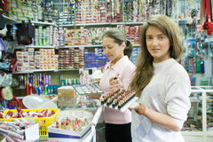 Zwei Frauen wählt Kosmetik am Kosmetiksystem lizenzfreies stockbild