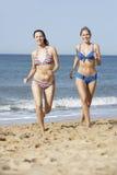 Zwei Frauen, welche die Bikinis laufen entlang Strand tragen Stockfotos