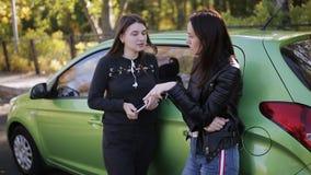 Zwei Frauen, welche die Stellung am Stamm des grünen Autos sprechen stock footage
