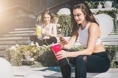 Zwei Frauenathleten in der Sportkleidung sitzen auf Bank, sich entspannen nach Sport ausbildend, benutzen Smartphones, hören Musi stockfotografie