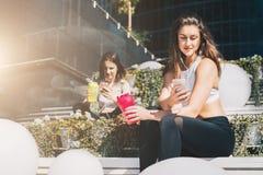 Zwei Frauenathleten in der Sportkleidung sitzen auf Bank, sich entspannen nach Sport ausbildend, benutzen Smartphones, hören Musi stockbilder