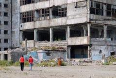 Zwei Frauenfiguren auf dem Hintergrund eines verlassenen hohen Gebäudes lizenzfreie stockfotografie