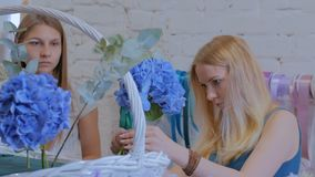 Zwei Frauenfloristen, die großen Blumenkorb mit Blumen am Blumenladen machen stock video footage