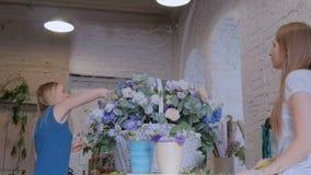 Zwei Frauenfloristen, die großen Blumenkorb mit Blumen am Blumenladen machen stock video
