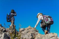 Zwei Frauenwanderer, die in Richtung zur Spitze des Berges klettern Stockfotos
