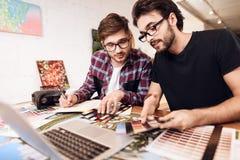 Zwei Freiberuflermänner, die Farbmuster auf Laptop auf Schreibtisch betrachten Stockbild