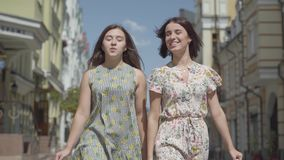 Zwei freudige Frauen mit Einkaufstaschen gehend durch Stadtstraße Junge Mädchen, die das stilvolle Sommerkleidergenießen tragen stock video footage