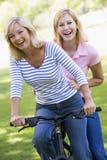 Zwei Freunde auf einem Fahrrad draußen lächelnd Lizenzfreie Stockfotografie