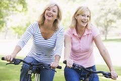 Zwei Freunde auf Fahrrädern draußen lächelnd Lizenzfreie Stockfotos