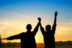 Zwei Freunde auf Sonnenuntergang-Hintergrund Lizenzfreie Stockbilder