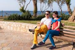 Zwei Freunde, die auf der Bank nach einem Spaziergang sich entspannen Lizenzfreie Stockfotos