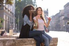 Zwei Freunde, die auf der Straße und den Schlagbubles sitzen Schwarzes Mädchen mit ihrem Freund lizenzfreie stockbilder