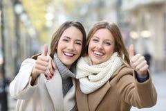 Zwei Freunde, die an der Kamera mit den Daumen oben im Winter lächeln Stockfoto
