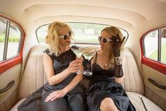 Zwei Freunde, die im Retro- Auto sitzen und mit coctails feiern Lizenzfreie Stockfotos