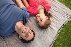 Zwei Freunde, die in Richtung des Himmels beim Lügen auf einer Steppdecke blicken Lizenzfreie Stockfotos