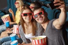 Zwei Freunde, die selfie im Kino machen lizenzfreie stockbilder