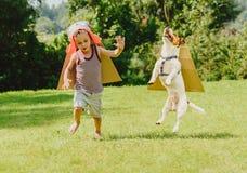 Zwei Freunde, die Senkrechtstarter mit Pappflügeln spielen Stockfotos